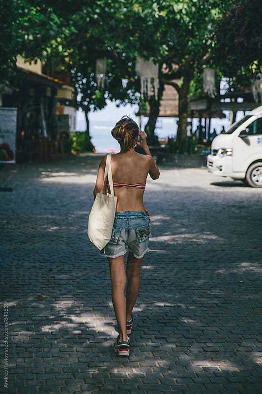 Back view of young woman walking to the beach by Andrey Pavlov for Stocksy United