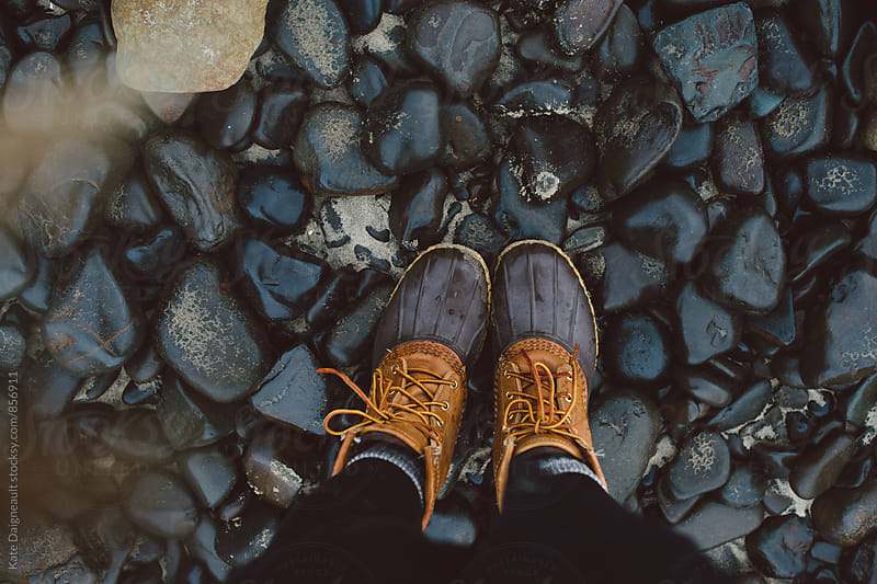 Pair of duck boots on dark colored beach rocks by Kate Daigneault for Stocksy United