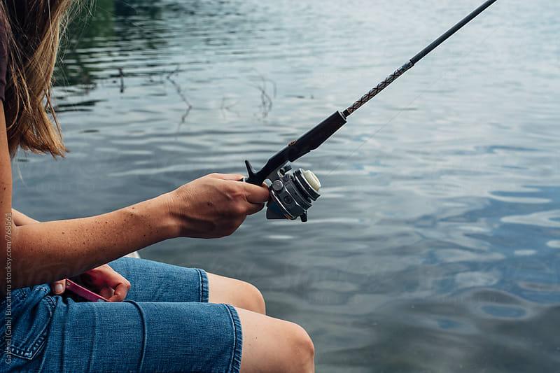 Woman fishing by a lake by Gabriel (Gabi) Bucataru for Stocksy United