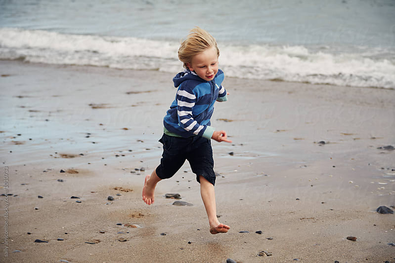 Child running on the beach by sally anscombe for Stocksy United