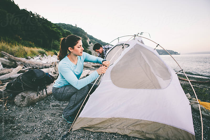 Couple setting up a tent on the beach by Suprijono Suharjoto for Stocksy United