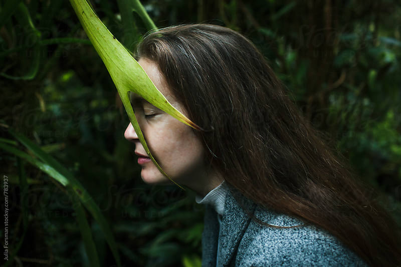 Woman rests her face against a large leaf. by Julia Forsman for Stocksy United