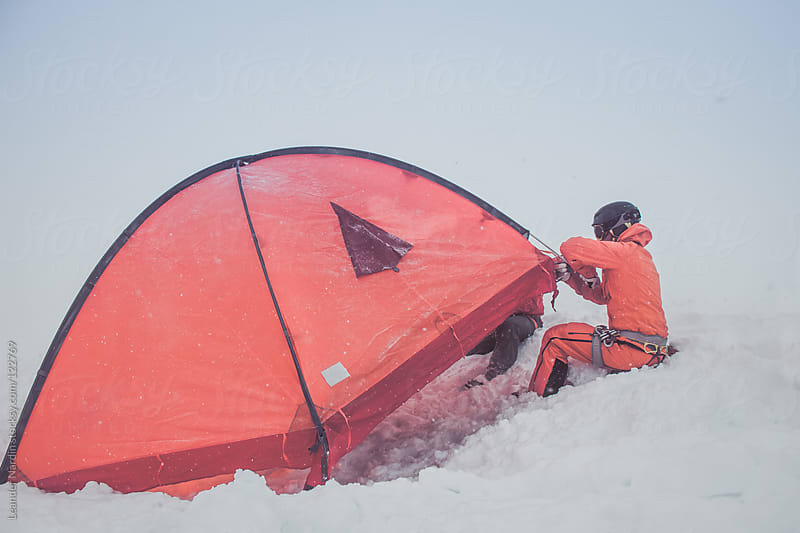 young male freeskier is trying to set up an orange tent during a snowstorm by Leander Nardin for Stocksy United