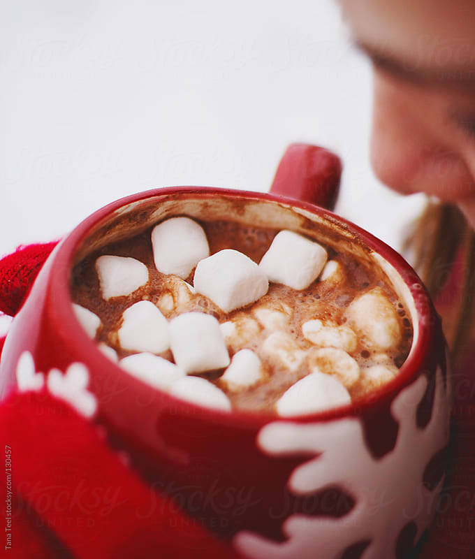 A girl holds a mug of hot cocoa with marshmallows by Tana Teel for Stocksy United