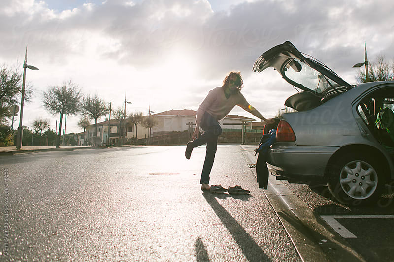 Man getting undressed on a parking lot to get ready for a surf session by Denni Van Huis for Stocksy United
