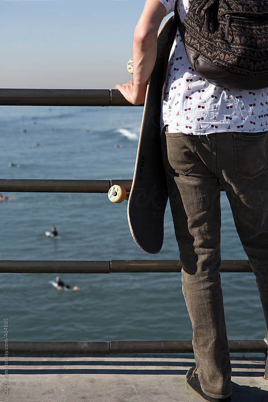 Young man with skateboard watching surfers on the pier by Curtis Kim for Stocksy United