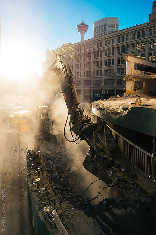 An excavator demolishes a parking structure. by Riley Joseph for Stocksy United