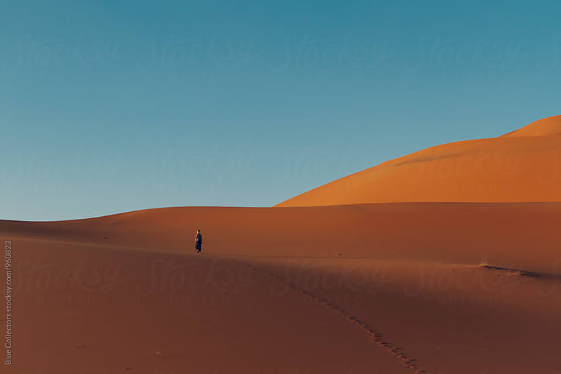 Woman walk into the Desert dunes landscape by Jordi Rulló for Stocksy United
