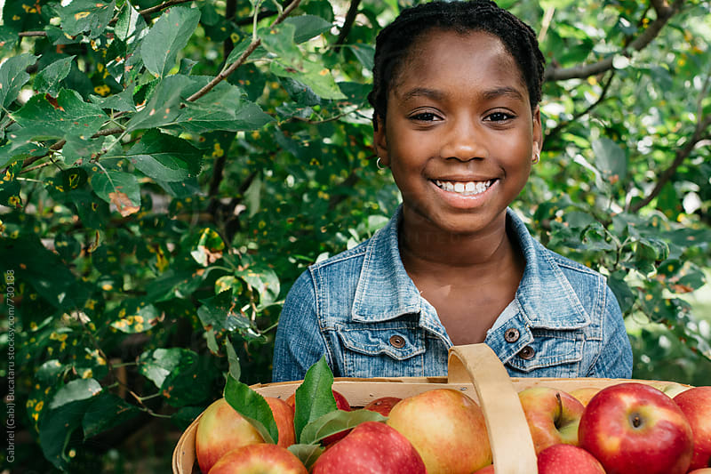 Smiling African American girl with basket of apples by Gabriel (Gabi) Bucataru for Stocksy United
