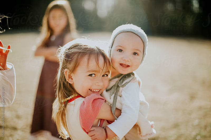Children smiling in the sunshine by Michelle Gardella for Stocksy United