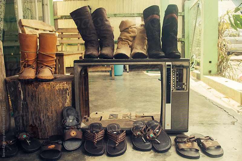 Leather shoes and boots displayed on old tv in leather shop by Soren Egeberg for Stocksy United