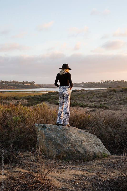 Back view of woman standing on rock in an open meadow by Curtis Kim for Stocksy United