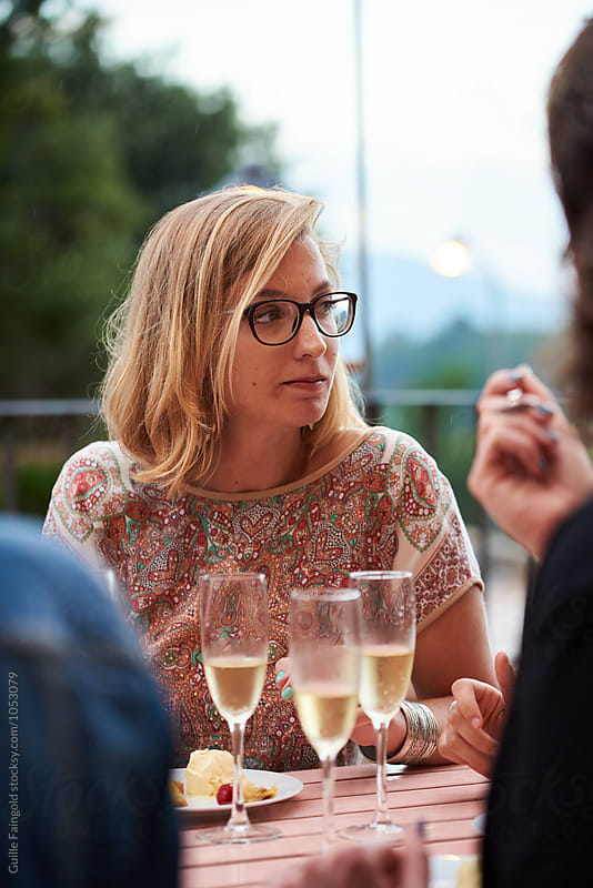 short-haired blonde in glasses having dinner with friends by Guille Faingold for Stocksy United