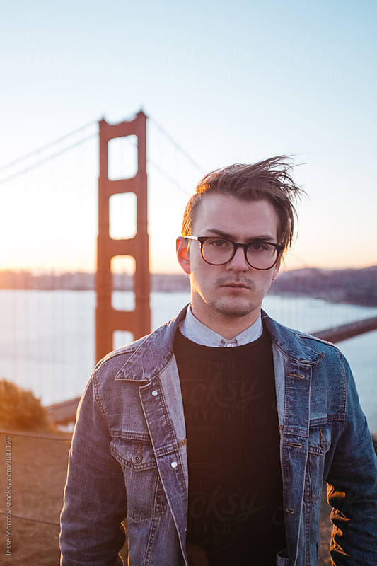 portrait of young male in front of golden gate bridge by Jesse Morrow for Stocksy United
