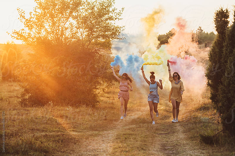 Happy Girls Running With Smoke Bombs by Lumina for Stocksy United