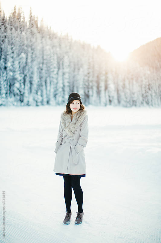 Young stylish beautiful girl smiling on snow covered winter lake by Luke Liable for Stocksy United