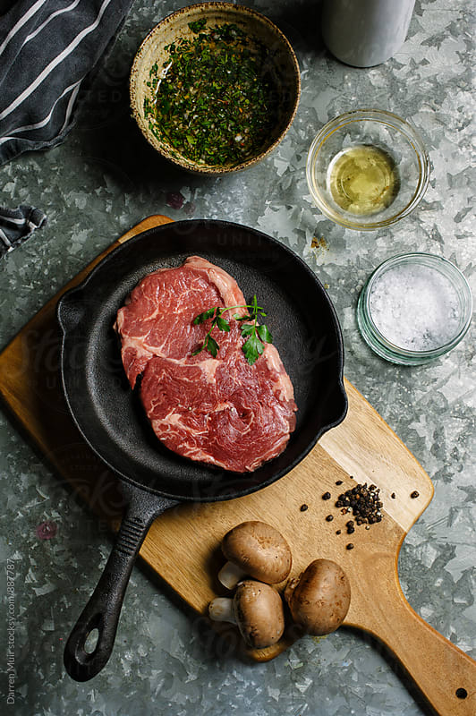 Beef steak in a cast iron pan,surrounded by ingredients for preparing the meat. by Darren Muir for Stocksy United