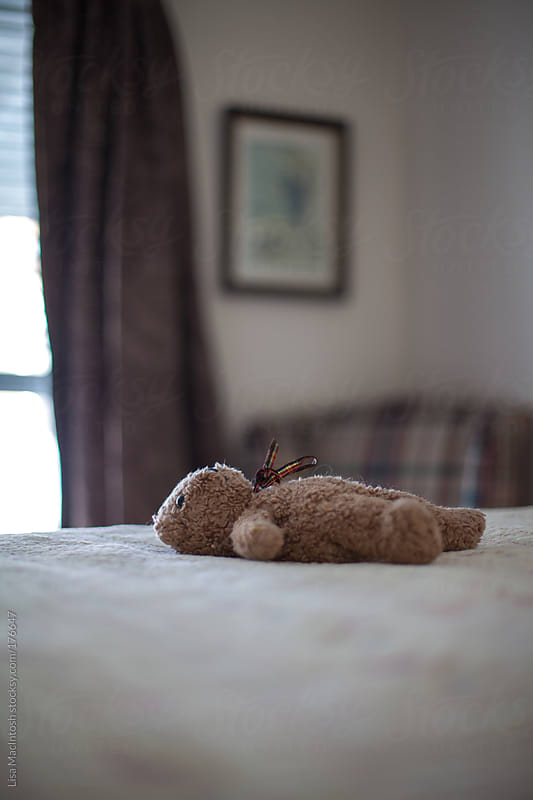 child's vintage teddy bear lying on on bed by Lisa MacIntosh for Stocksy United
