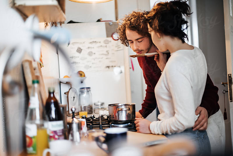 Young couple cooking together in a kitchen. by minamoto images for Stocksy United