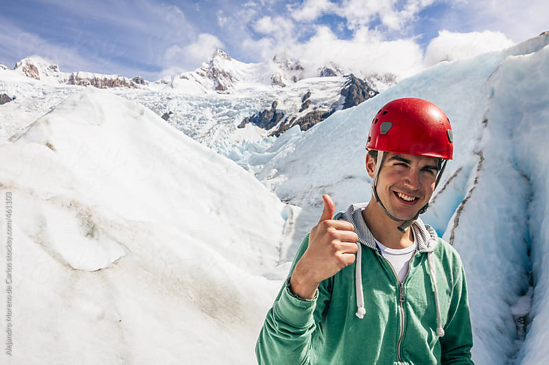 Young happy man with ice climbing equipment on a glacier. Glacier Torre, El Chaltén, Argentina, Patagonia by Alejandro Moreno de Carlos for Stocksy United
