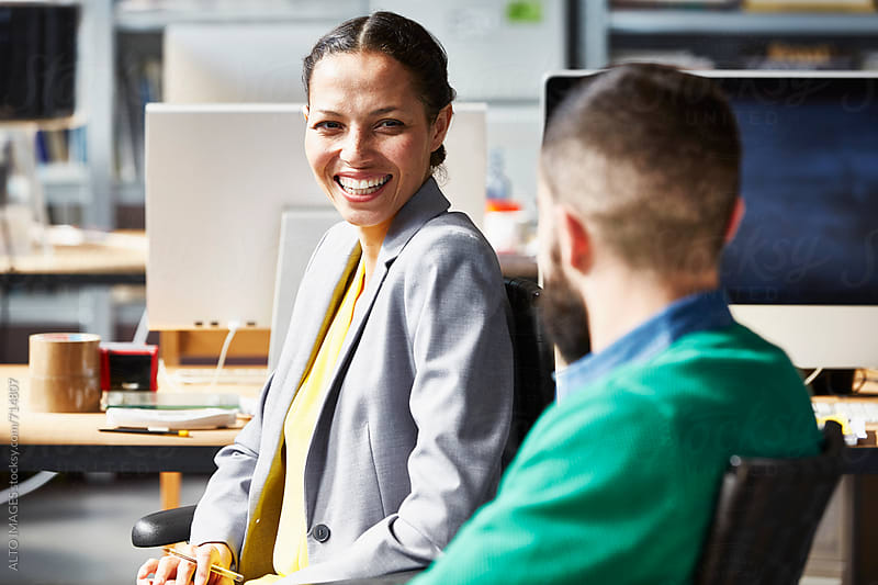 Smiling Businesswoman With Colleague In Office by ALTO IMAGES for Stocksy United