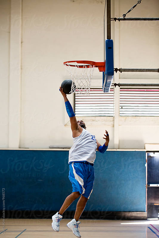 Man going up for a layup in the gym by Curtis Kim for Stocksy United