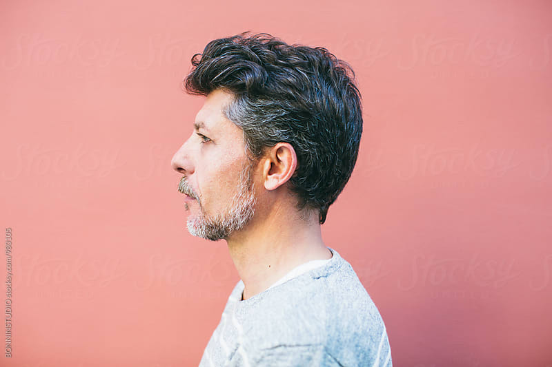 Side view of a mature man in front of colorful wall. by BONNINSTUDIO for Stocksy United