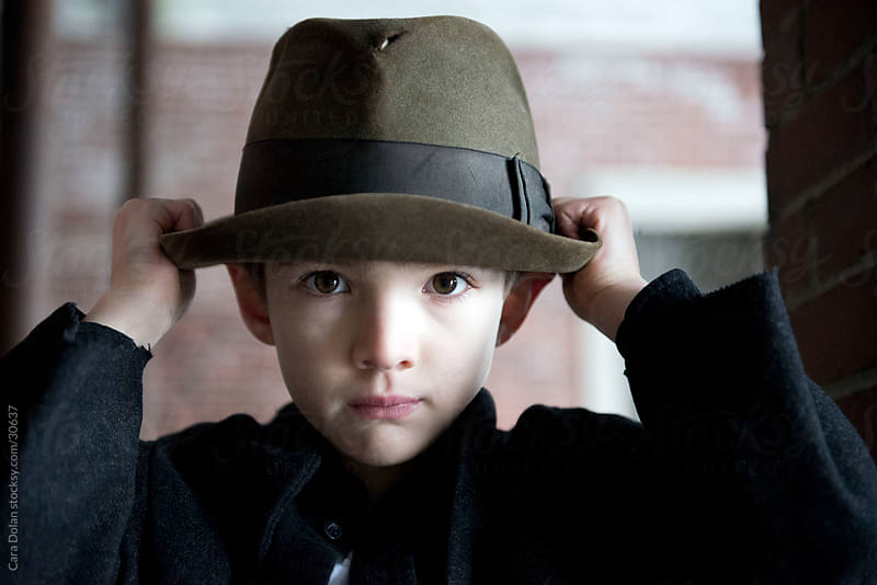 Boy adjusts his hat by Cara Dolan for Stocksy United