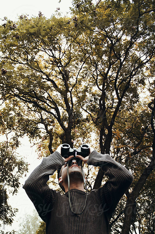 Man looking through binoculars in nature by Jovana Rikalo for Stocksy United