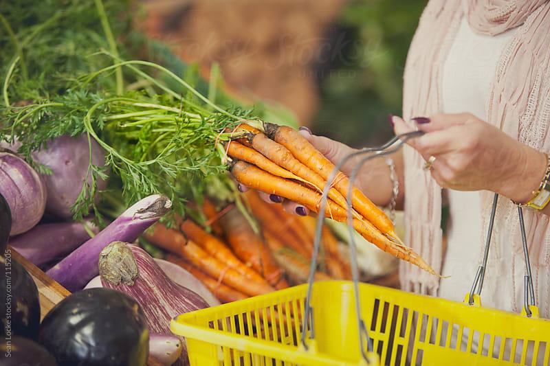 Market: Woman Choosing Carrots From Bin by Sean Locke for Stocksy United