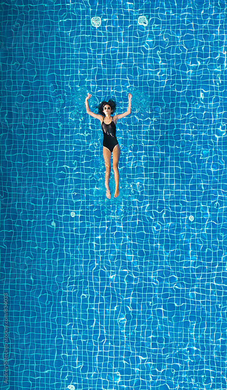 Attractive young woman in black swimsuit floating in the pool/look form above. by Marko Milanovic for Stocksy United