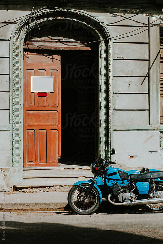 Vintage motorcycle in front of the open door by Natasa Kukic for Stocksy United