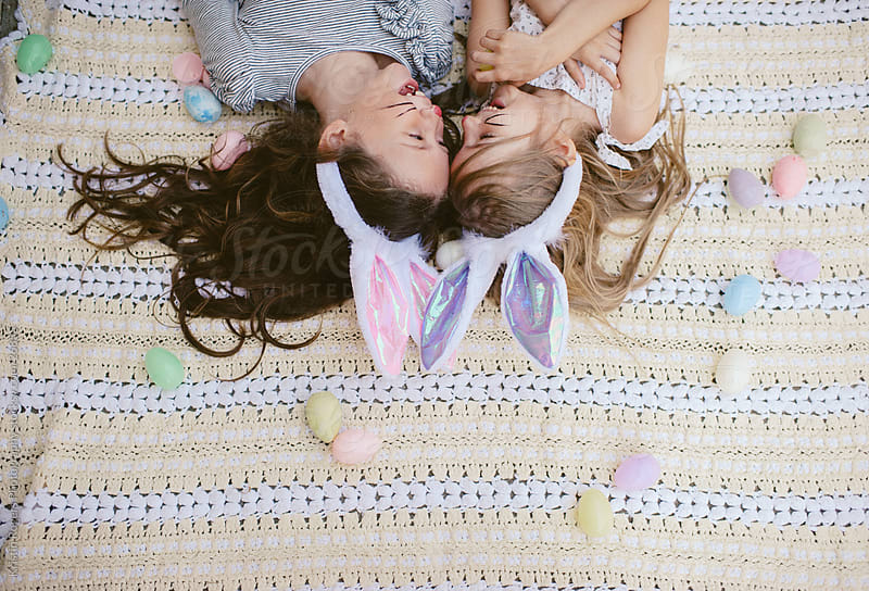 Two little friends with bunny ears on laying around Easter eggs by Kristin Rogers Photography for Stocksy United