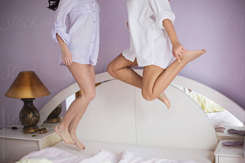 Two female friends jumping on bed by Jovana Rikalo for Stocksy United