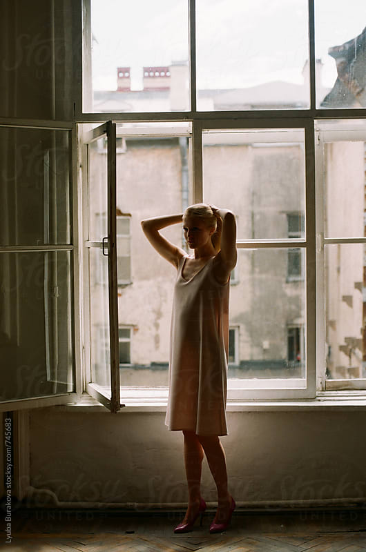 Young woman standing against window by Lyuba Burakova for Stocksy United