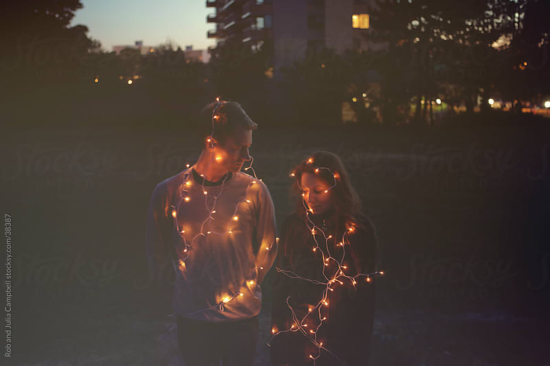 Couple  covered in lights by Rob and Julia Campbell for Stocksy United