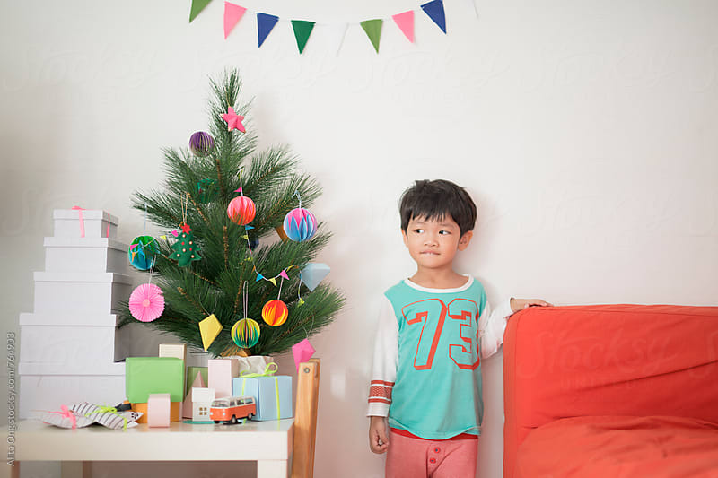 Mischievous  kid standing next holiday tree by Alita Ong for Stocksy United