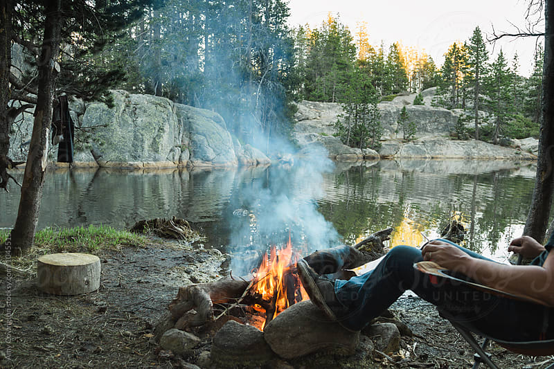 Man sitting in front of a campfire by Amy Covington for Stocksy United