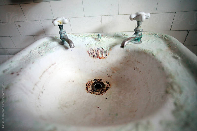 Dirty porcelain bathroom sink in abandoned house by Dina Giangregorio for Stocksy United