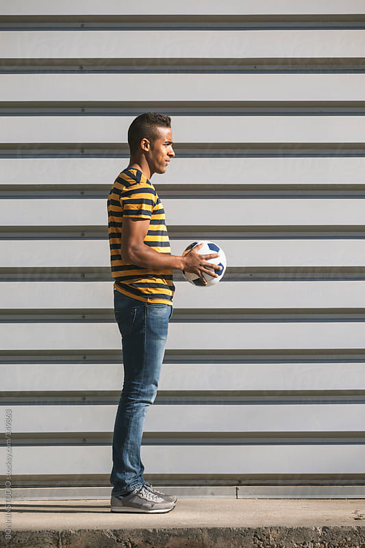 Black man standing with soccer ball on cityscape. by BONNINSTUDIO for Stocksy United