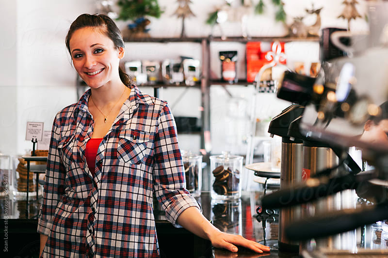 Bakery: Cheerful Barista Stands Near Espresso Machine by Sean Locke for Stocksy United