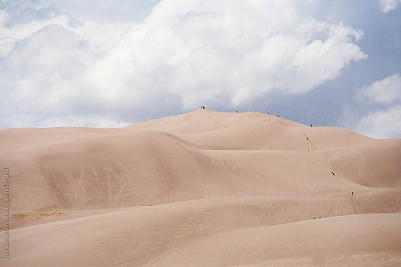 Big fluffy clouds over the silky beige landscape of the Colorado Sand Dunes, walked on by distant silhouetted people.  by Kaat Zoetekouw for Stocksy United