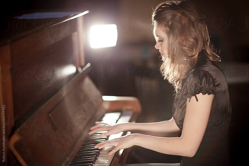 Young woman playing and old piano by Robert Kohlhuber for Stocksy United