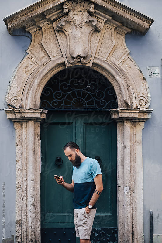 Bearded Man Standing in front of the Old Green Door by Katarina Radovic for Stocksy United