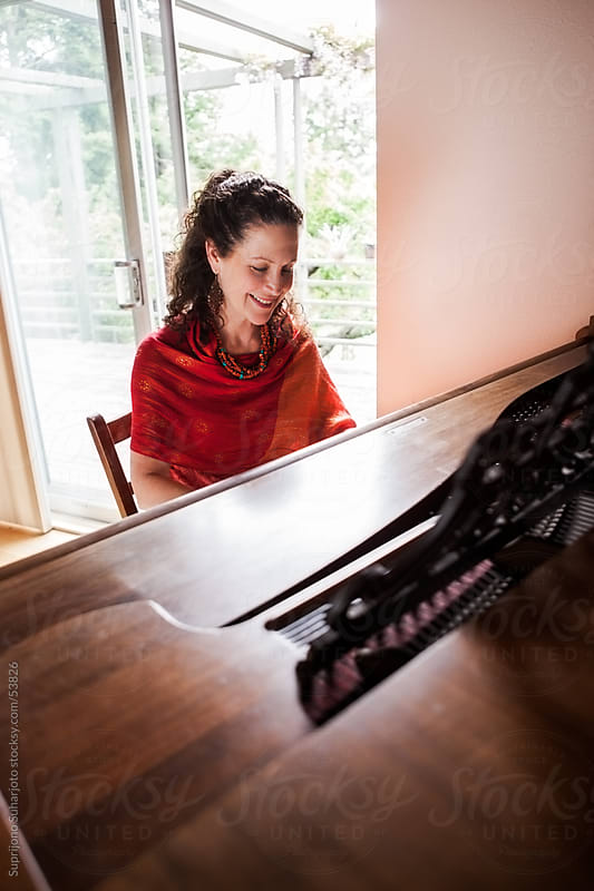 Middle age woman playing piano at home by Suprijono Suharjoto for Stocksy United