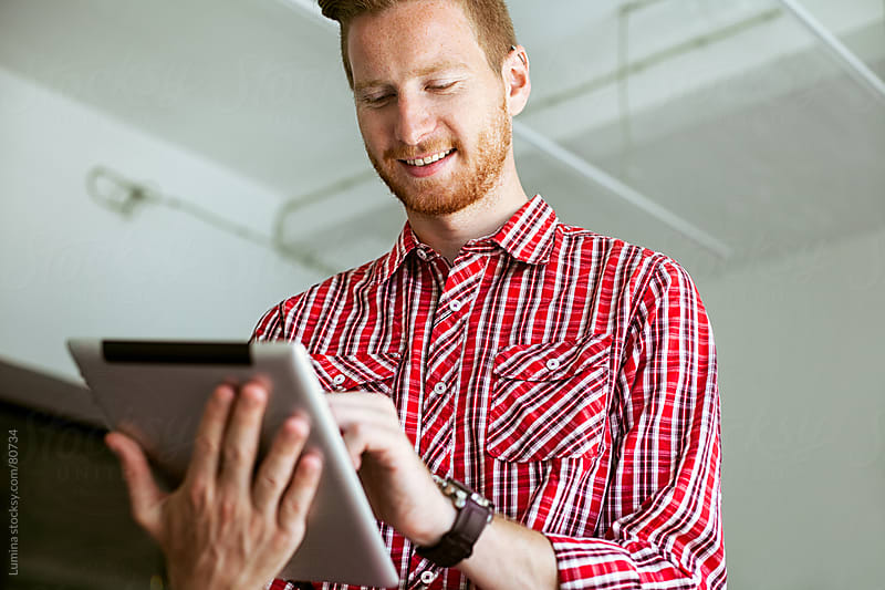 Ginger Businessman Using a Digital Tablet by Lumina for Stocksy United