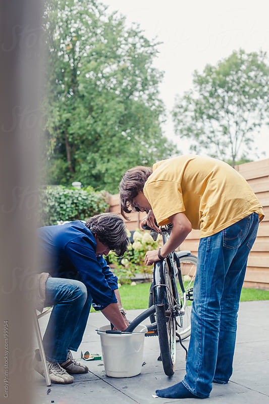 Father teaching his teenage son how to repair a flat tire on his bicycle by Cindy Prins for Stocksy United