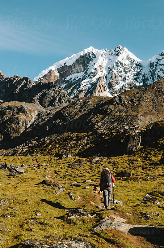 Female trekker walking up a valley with snow capped peaks, Everest Region, Nepal. by Thomas Pickard for Stocksy United