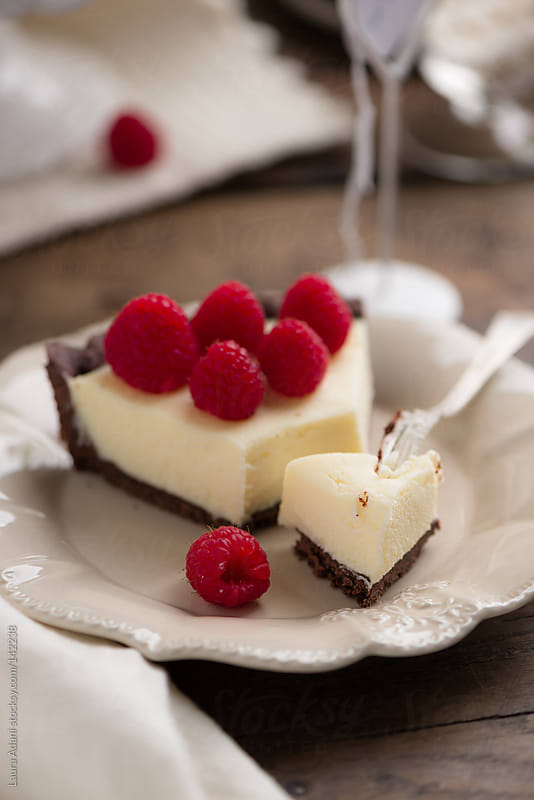 a slice of chocolate cheese tart with raspberries by Laura Adani for Stocksy United