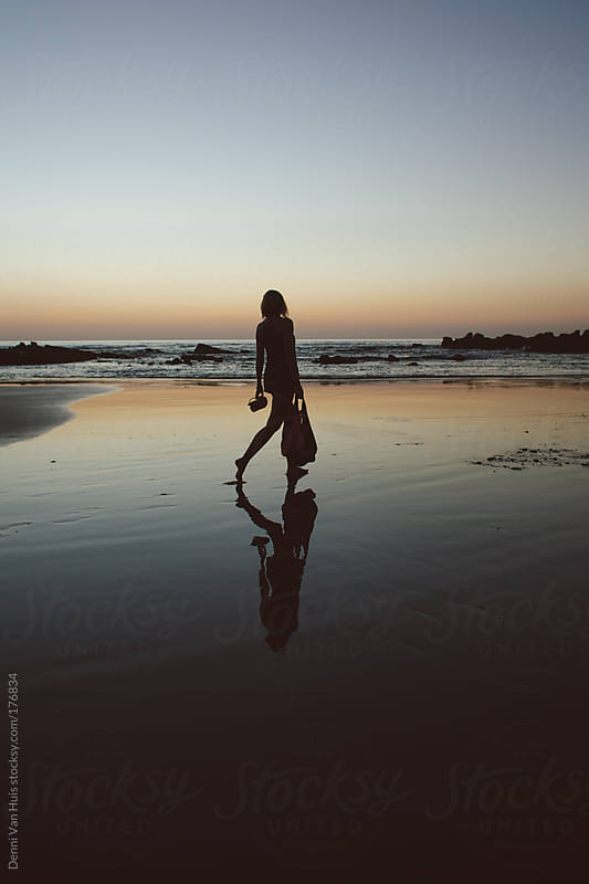 Young woman walks on the beach during sunset by Denni Van Huis for Stocksy United